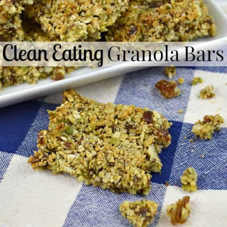 crumbly granola bar on blue and white check tablecloth with tray of granola bars in the background