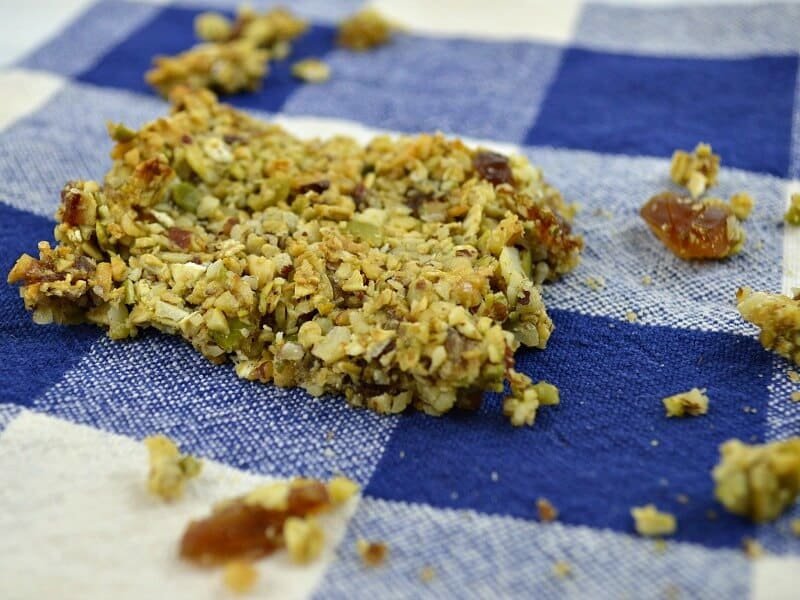 homemade granola bar with crumbs on blue napkin