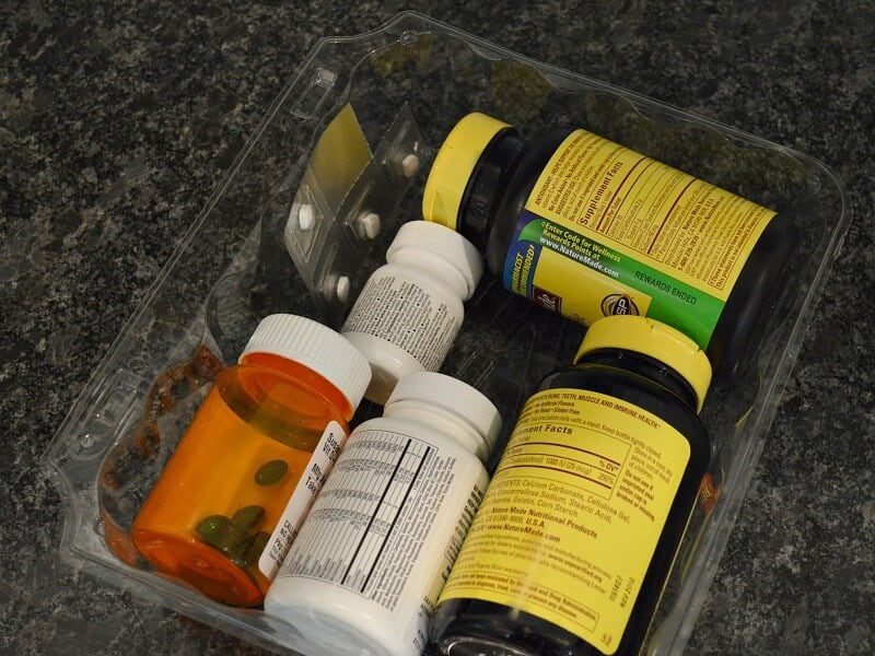 clear container holding bottles of vitamins and medication