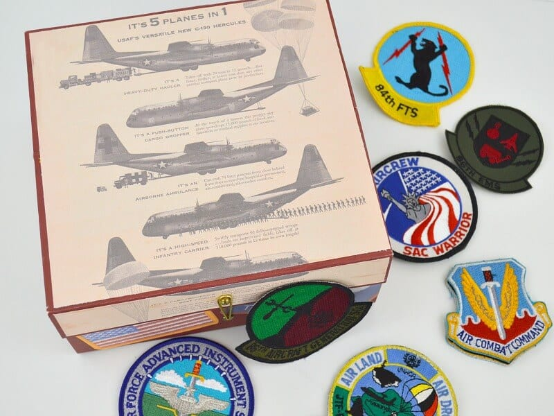 overhead view of box with retro planes and flight patches scattered on table
