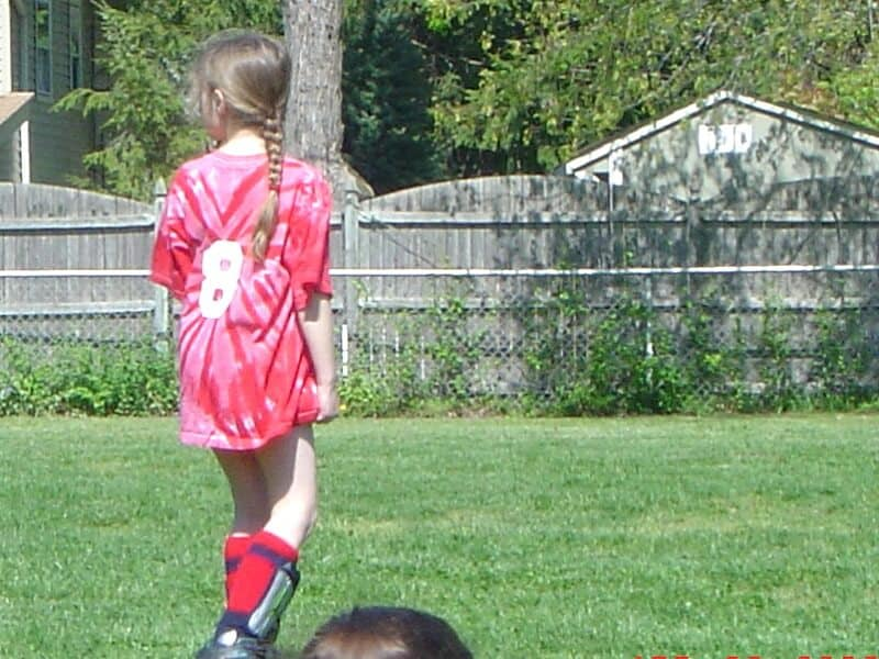 back of girl in red jersey playing soccer