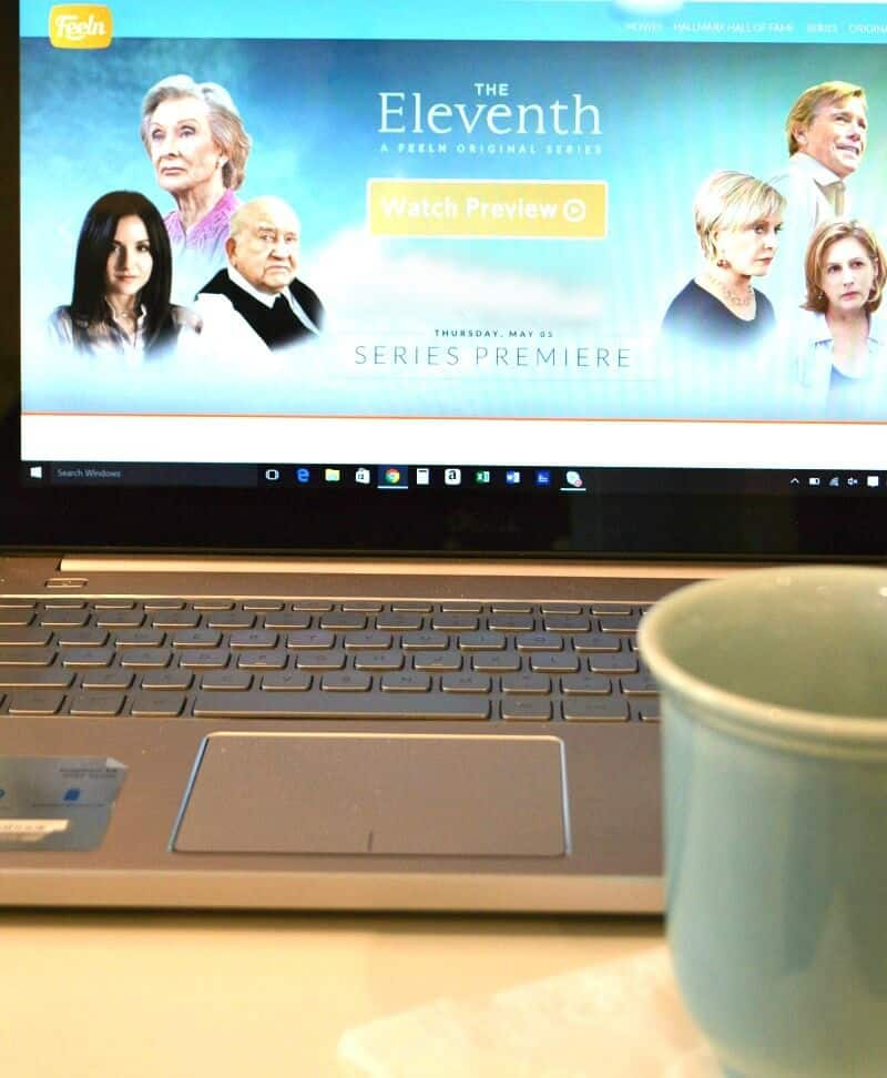 blue coffee mug in front of laptop with movie on screen