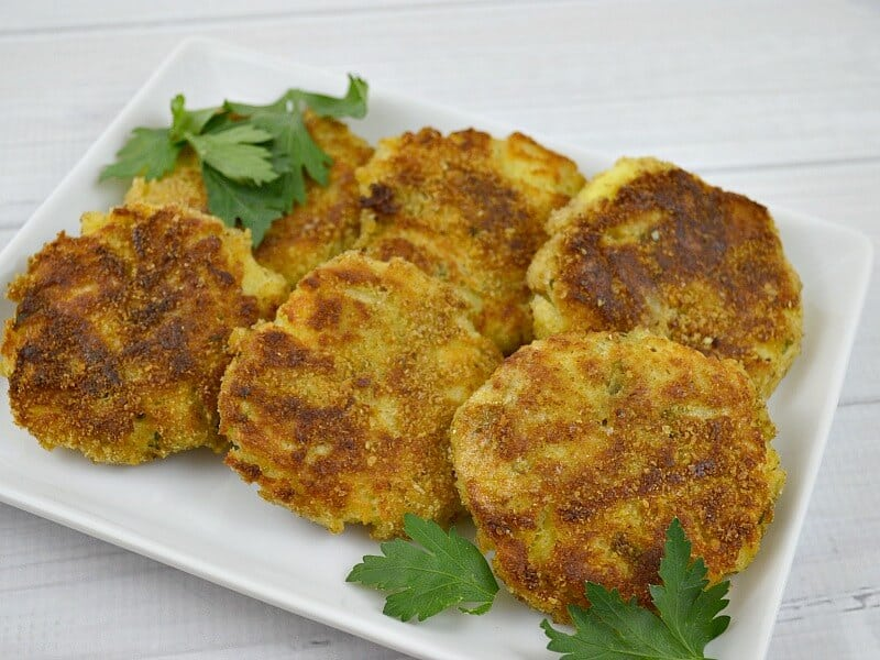 overhead view of 6 potato pancakes on white plate on white wood table