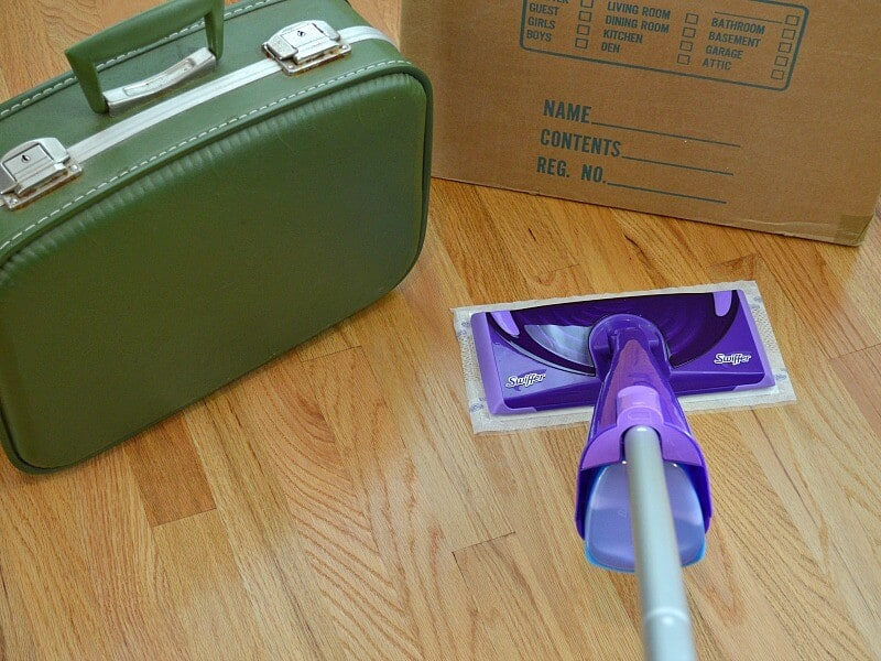 moving box, with green suitcase and mop on wood floor