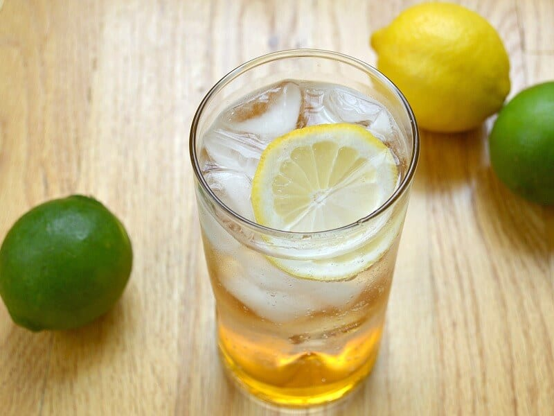 Glass of water with slice of lemon on wood table with limes and a lemon in the background.