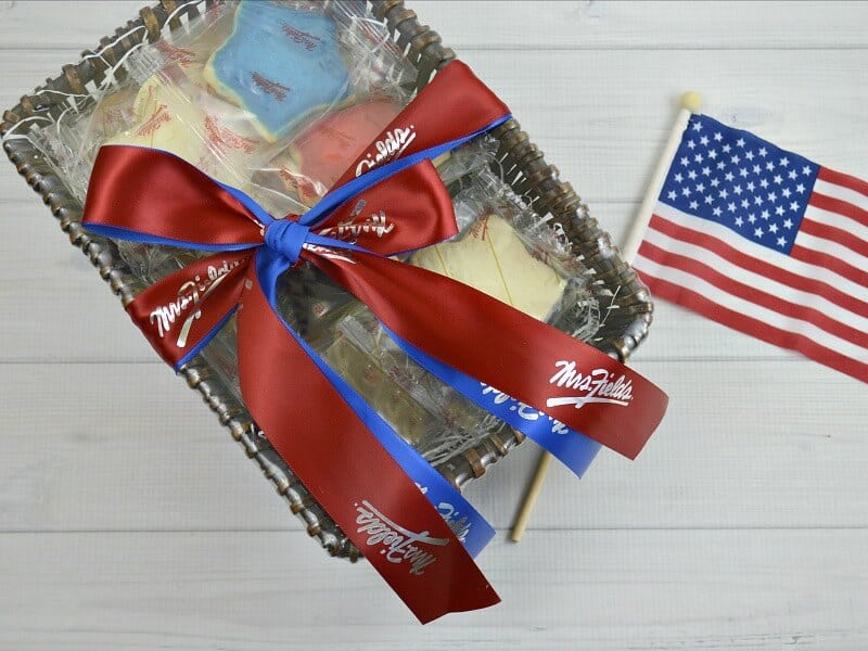 basket with red and blue bow and American flag on white wood table