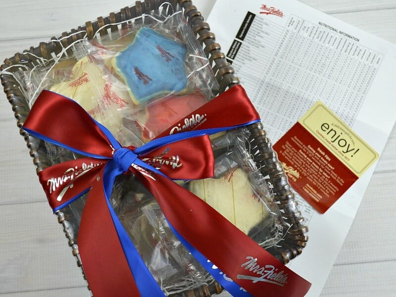 overhead view of brown basket filled with cookies and tied with a red and blue bow
