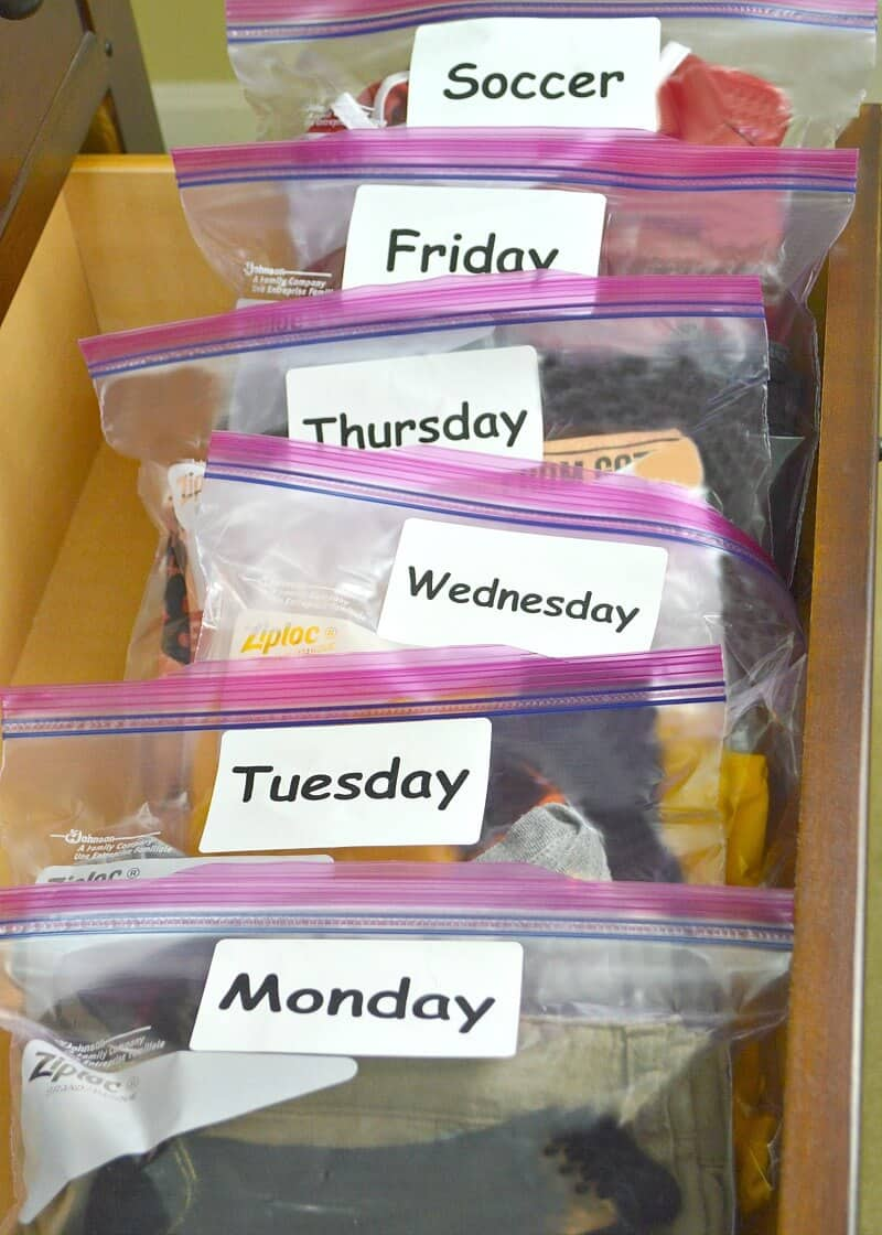 neatly filed plastic bags of clothing with white labels with days of the week