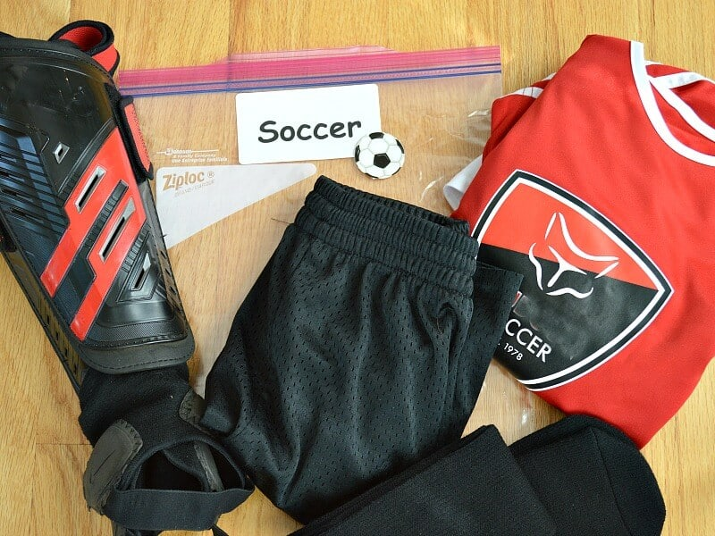 "plastic bag with white label saying ""soccer"" with soccer uniform and shin guards"