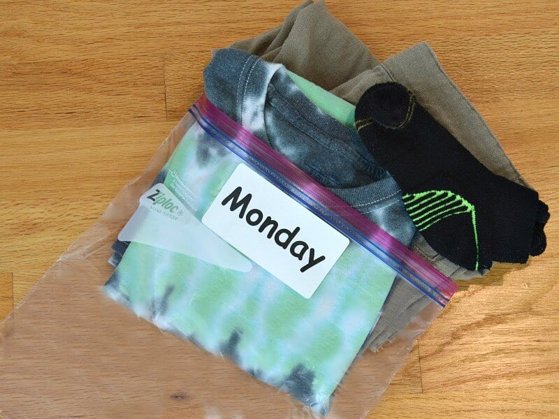 "pile of neatly folded clothes halfway in plastic bag with label saying ""Monday"""