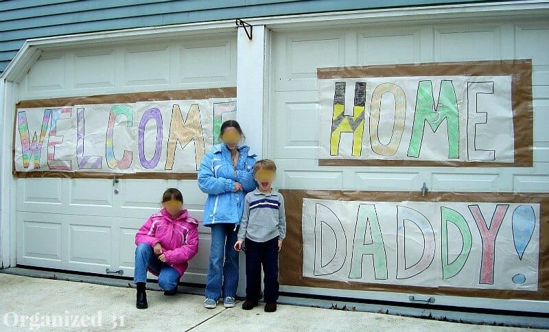 """military kids in front of """"welcome home daddy"""" sign on garage"""
