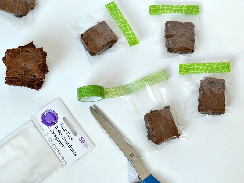 brownies in clear bags decorated with green washi tape and pair of blue scissors