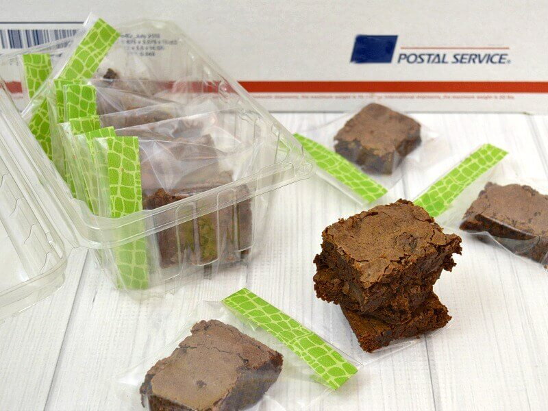 brownies in clear decorated bags in front of red and blue shipping box
