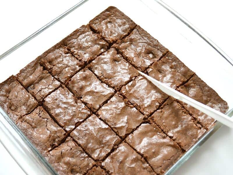 glass baking pan with brownies but into squares and white knife