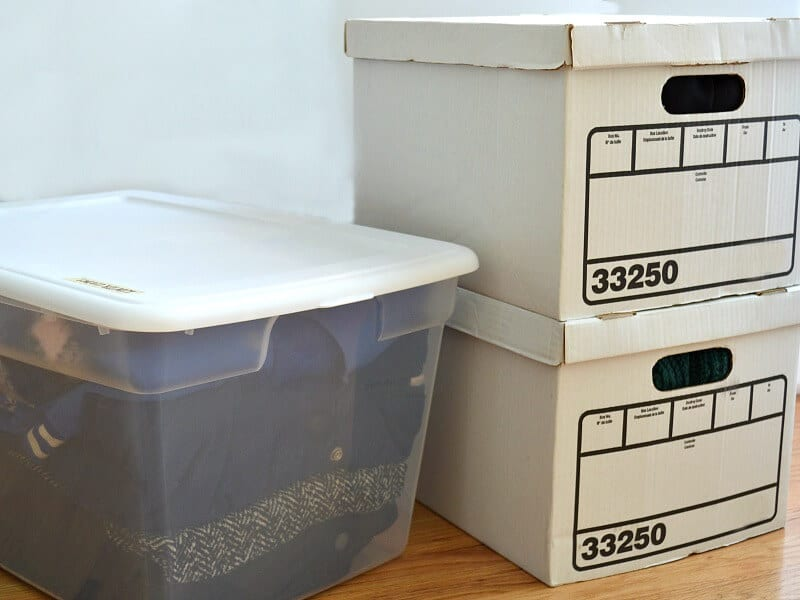 clear storage bin packed with clothing next to 2 stacked white boxes with handles