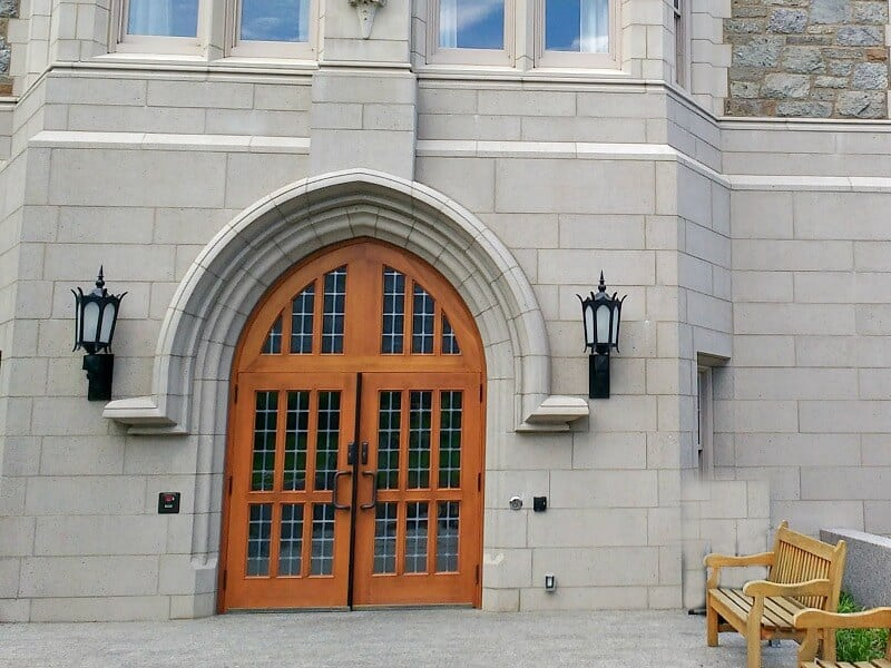 large wood door in stone building with benches to the right side