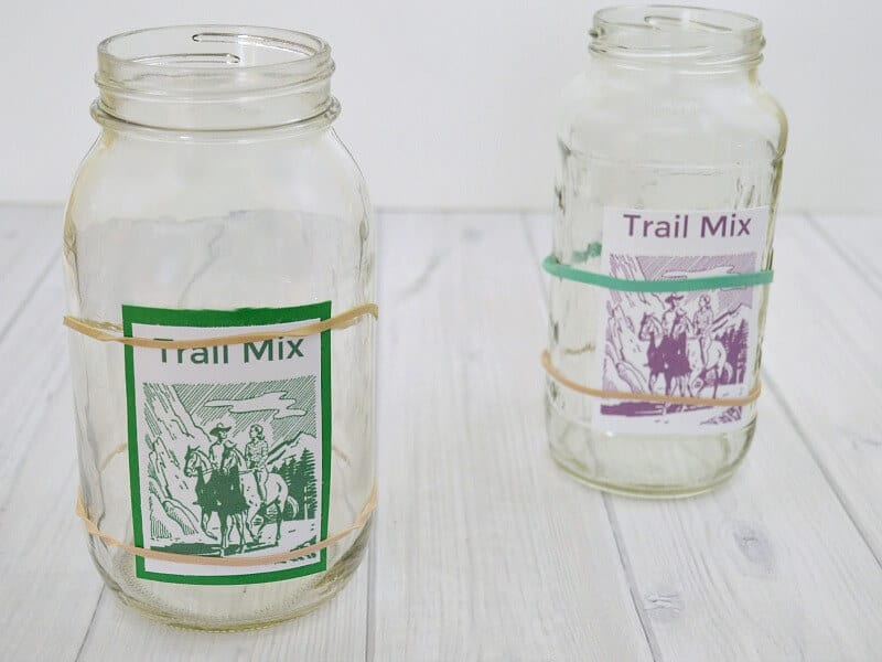 2 glass jars with colorful labels with rubber bands holding labels in place