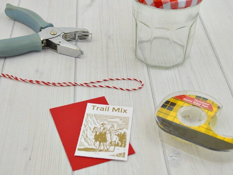 hold punch, glass jar with red checked lid, roll of tape and red trail mix label on white wood table