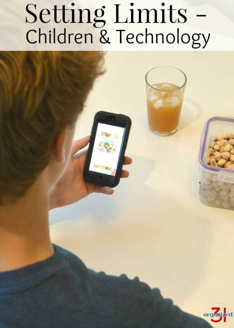 boy looking at cell phone screen with snacks and cup of juice nearby