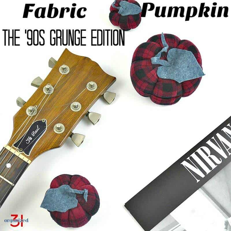3 red and black plaid fabric pumpkins on white table with guitar and black and white record album cover