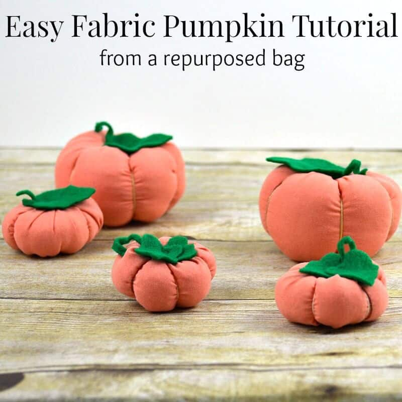 f5 different sized orange fabric pumpkins with green felt leaves on wood table