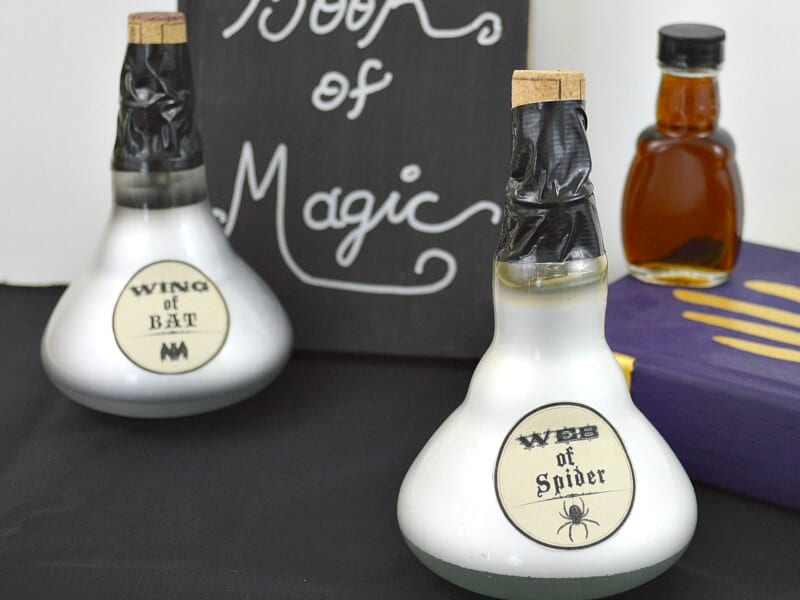 2 potion bottles from upcycled light bulbs with magic book in background