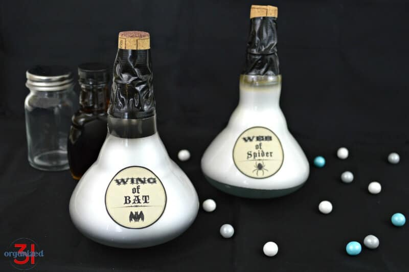Close up of 2 potion bottles with empty bottles in the background