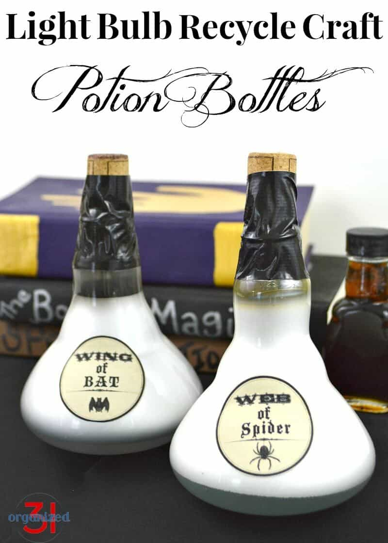 2 Potion Bottles made from upcycled light bulbs siting on stack of spell books