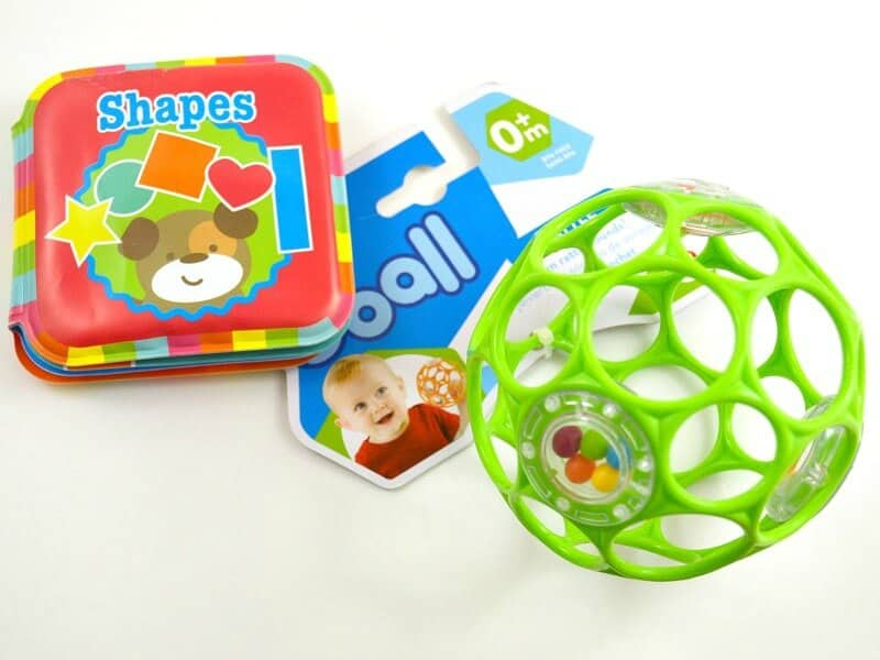 brightly colored vinyl baby book and plastic ball on white table