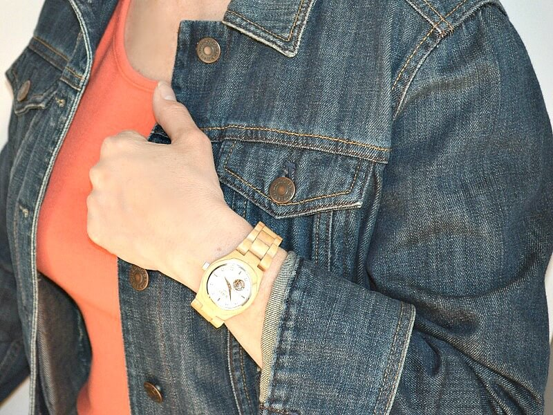 woman wearing wood watch and jean jacket