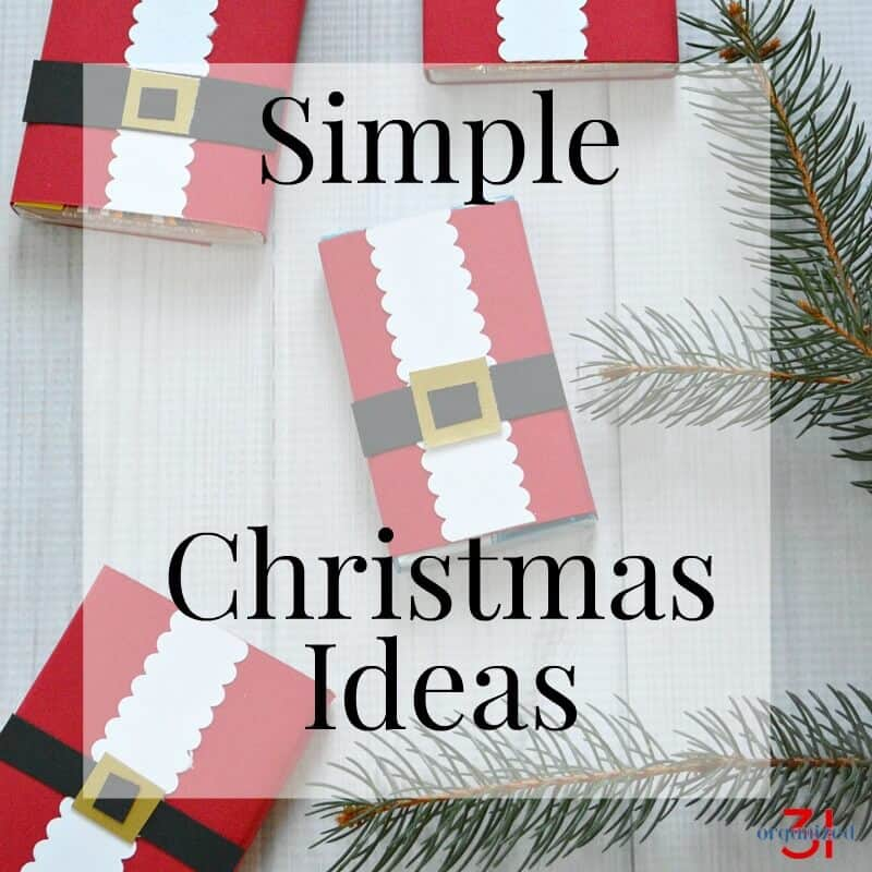 4 DIY paper craft Santa suits on white table with pine boughs