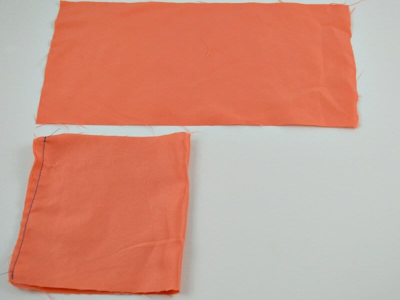 rectangle of orange fabric and piece of fabric folded in half and one sewn seam