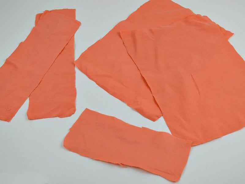 piles of rectangles of orange fabric on white table