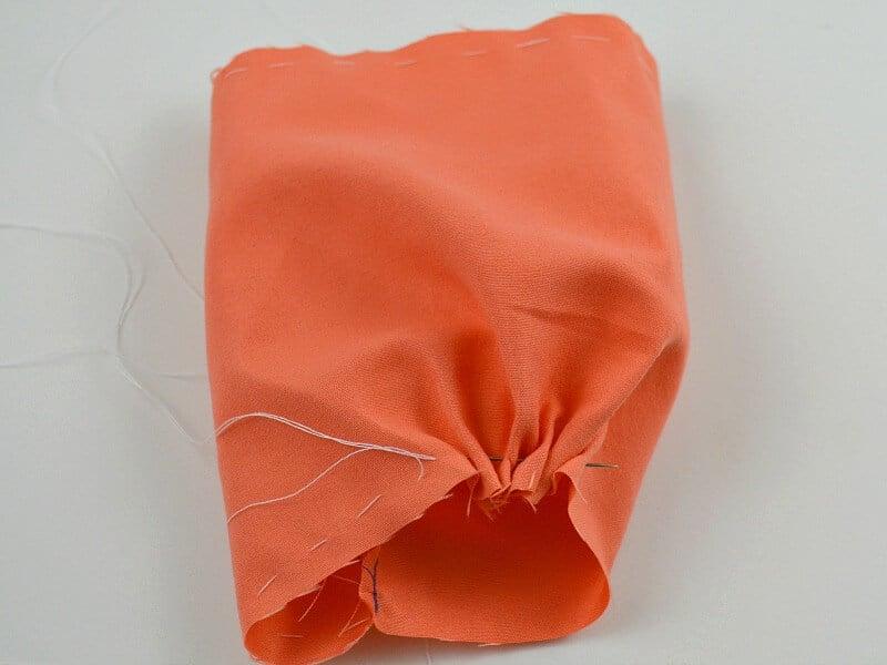 needle with white thread gathering one side of orange fabric tube
