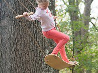 child standing on swing by tree