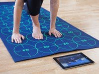 person with one foot and two hands on blue mat