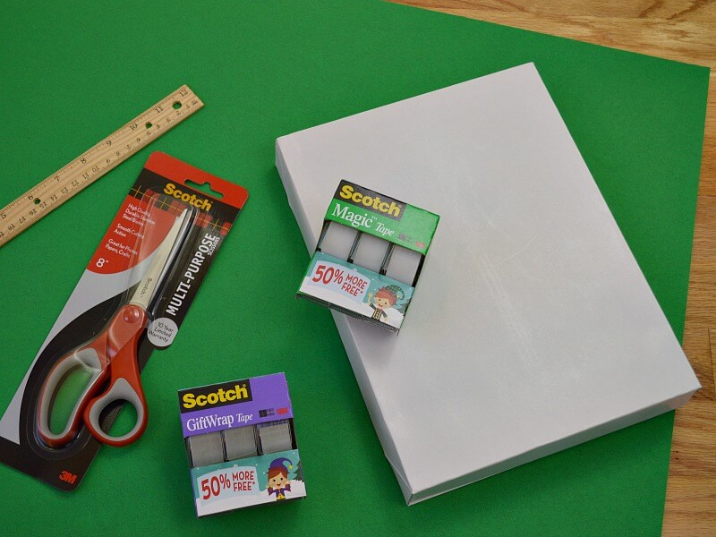 green paper with ruler, scissors, tape and white box