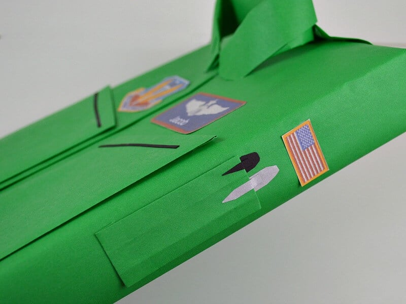 sideview of box wrapped to look like a flight suit showing shoulder pocket holding pens