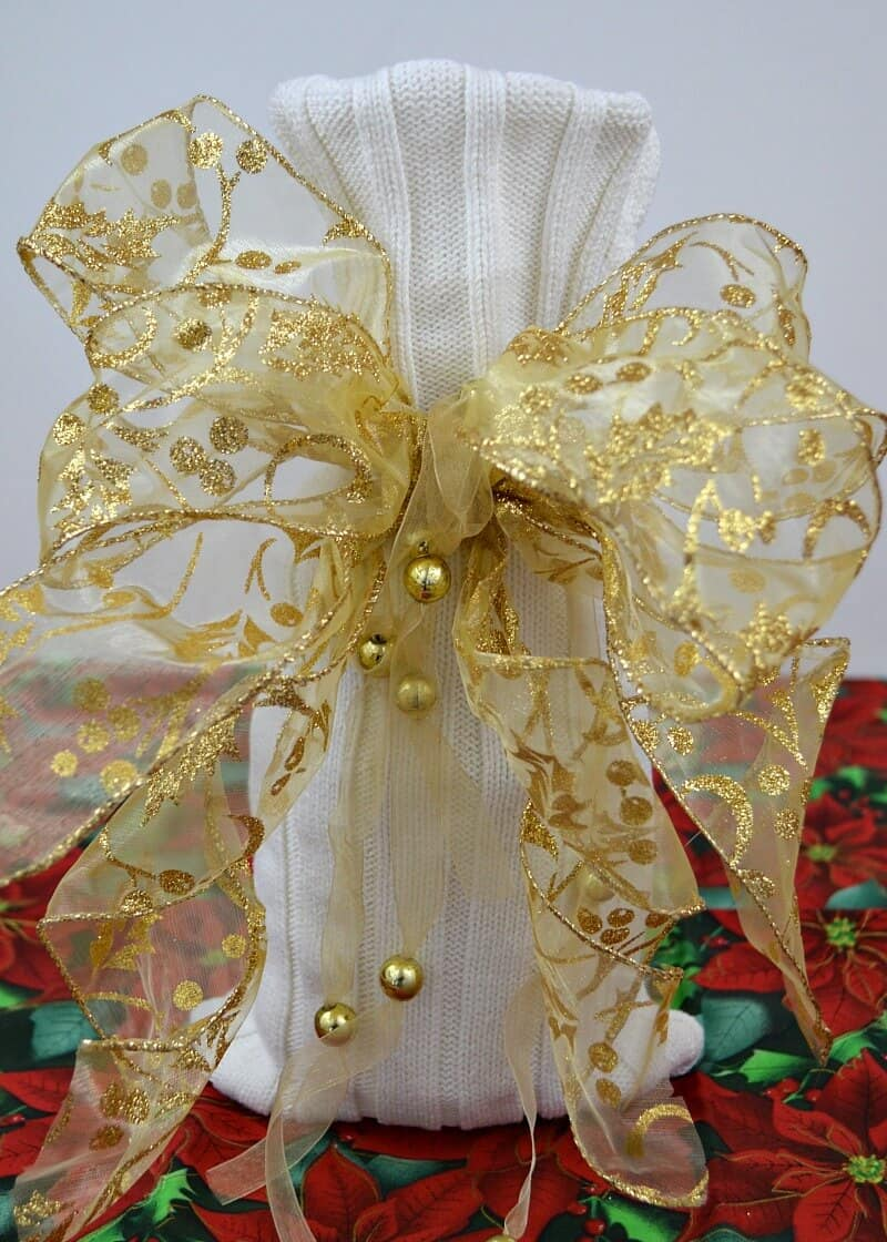 white knit gift bag with large gold bow on Christmas tablecloth