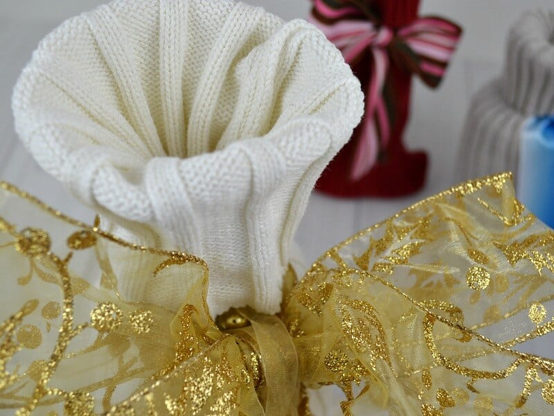 close up of top of white knit gift bag with large gold bow