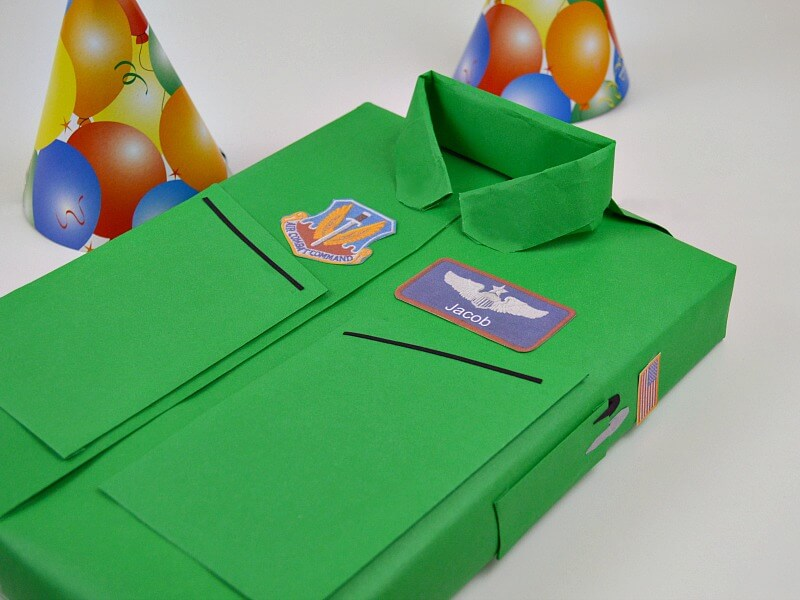 box wrapped to look like green Air Force flight suit with 2 birthday hats in the background