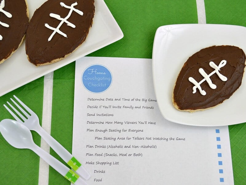 football cookies on plates on football field tablecloth with the homegating preparation checklist