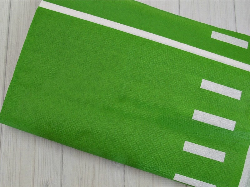 folded green with white lines table cloth that looks like a football field