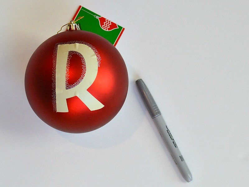 """R"" sticker on red Christmas ornament ball and grey marker on white table"