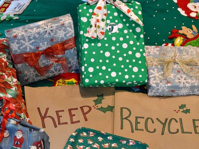 "many festively wrapped Christmas gifts with 2 brown paper sacks labeled ""keep"" and ""recycle"""