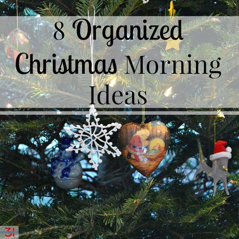 close up of ornaments hanging on Christmas tree including white star, heart shape with Santa kneeling in front of baby in manger an dog with Santa hat with title text overlay reading 8 Organized Christmas Morning Ideas