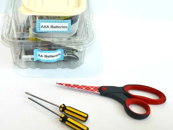 containers of batteries stacked with red scissors and 2 small screw drivers