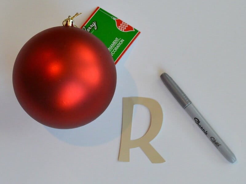 "red ornament ball, silver marker and ""R"" sticker on white table"