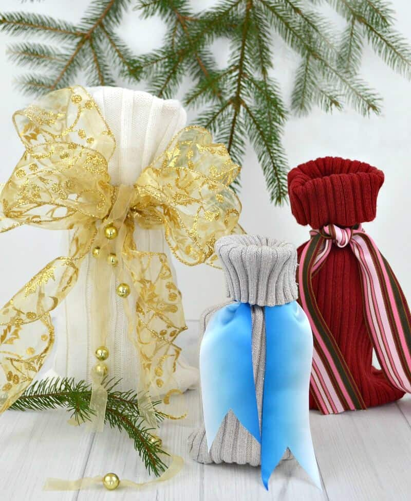 3 knit gift bags with large ribbons and pine branches on white wood table
