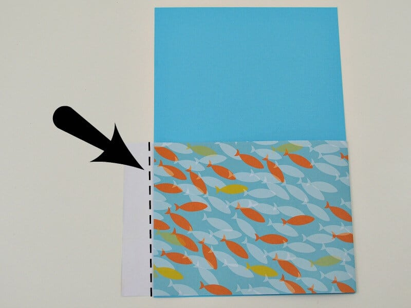 DIY pocket folder in blue with fish motif and arrow pointing to edge of paper